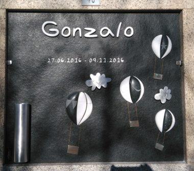 Lapida infantil con representación de globos simbolicos