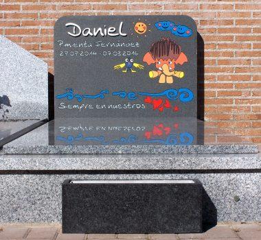 Lápida infantil, cabezal de tumba de suelo. Nuestro trabajo es el cabezal de la tumba donde se representa la ilustración infantil y la jardinera en granito negro flameado con vaso interior de aluminio colocado al pie de la tumba.