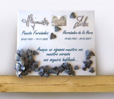 Lápida de diseño elegante y vanguardista, con corazones grabados y envejecidos, nombres manuscritos e incrustados, soporte de la lápida en mármol blanco de Carrara